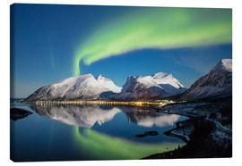 Tableau sur toile  Northern lights (aurora borealis) and stars light up the snowy peaks reflected in the cold sea, Berg - Roberto Moiola